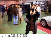 Купить «Happy pretty woman in fur coat shoots by phone at exhibition», фото № 28117435, снято 7 марта 2016 г. (c) Losevsky Pavel / Фотобанк Лори