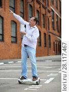 Купить «Happy man with tablet points up on GyroScooter near building at summer», фото № 28117467, снято 25 июня 2016 г. (c) Losevsky Pavel / Фотобанк Лори