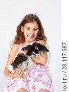 Купить «Happy smiling girl in dress holds funny rabbit and sits on chair in white studio», фото № 28117587, снято 20 ноября 2015 г. (c) Losevsky Pavel / Фотобанк Лори