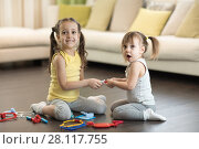 Conflict between little sisters. Kids are fighting, toddler girl takes toy, sibling relationships. Стоковое фото, фотограф Оксана Кузьмина / Фотобанк Лори