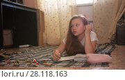 Girl teen who spend time at home drawing while lying on the floor. Стоковое видео, видеограф Константин Шишкин / Фотобанк Лори