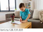 Купить «boy with notebook and pencils drawing at home», фото № 28131031, снято 4 ноября 2017 г. (c) Syda Productions / Фотобанк Лори