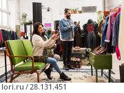 Купить «couple choosing footwear at vintage clothing store», фото № 28131451, снято 30 ноября 2017 г. (c) Syda Productions / Фотобанк Лори