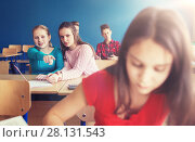 students gossiping behind classmate back at school. Стоковое фото, фотограф Syda Productions / Фотобанк Лори