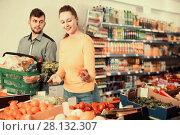 Купить «Positive couple choosing fresh vegetables in vegetable departmen», фото № 28132307, снято 20 января 2018 г. (c) Яков Филимонов / Фотобанк Лори