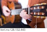 Купить «man in jacket playing an acoustic guitar», фото № 28132443, снято 29 марта 2017 г. (c) Яков Филимонов / Фотобанк Лори