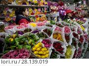 Купить «Женщина продает букеты весенних тюпанов на цветочном рынке в канун празднования Международного женского дня 8 Марта в городе Москве, Россия», фото № 28139019, снято 7 марта 2018 г. (c) Николай Винокуров / Фотобанк Лори