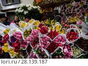 Купить «Женщина продает букеты весенних тюпанов на цветочном рынке в канун празднования Международного женского дня 8 Марта в городе Москве, Россия», фото № 28139187, снято 7 марта 2018 г. (c) Николай Винокуров / Фотобанк Лори