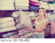 Купить «portrait of female customer choosing pillow in bedding section in shop», фото № 28139483, снято 22 мая 2018 г. (c) Яков Филимонов / Фотобанк Лори