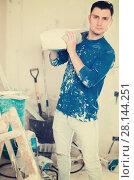 Купить «Young serious worker standing with bag of putty in hands», фото № 28144251, снято 21 мая 2017 г. (c) Яков Филимонов / Фотобанк Лори