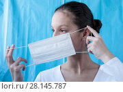 A girl doctor dresses a mask on a blue background. Стоковое фото, фотограф Катерина Белякина / Фотобанк Лори