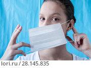 Купить «A girl doctor dresses a mask on a blue background», фото № 28145835, снято 18 февраля 2018 г. (c) Катерина Белякина / Фотобанк Лори