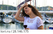 Купить «Portrait of charming brunette girl with a glass of red wine in outdoor restaurant with a marine yachts view», видеоролик № 28146175, снято 4 июня 2017 г. (c) Алексей Кузнецов / Фотобанк Лори