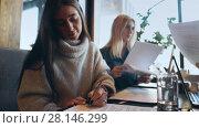 Купить «Young businesswoman freelancer signs documents in cafe», видеоролик № 28146299, снято 30 января 2018 г. (c) Виктор Аллин / Фотобанк Лори