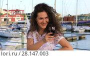Купить «Young attractive brunette woman drinking red wine at an outdoor restaurant and warmly waved to someone by hand», видеоролик № 28147003, снято 18 июня 2017 г. (c) Алексей Кузнецов / Фотобанк Лори