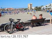 Люди отдыхают после велопрогулки. Пляж Playa de Las Vistas в городе Los Cristianos. Атлантический океан, остров Тенерифе, Канары, Испания (2016 год). Редакционное фото, фотограф Кекяляйнен Андрей / Фотобанк Лори