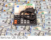 Steel police handcuffs, euro banknotes and calculator lying on the background of american dollars. Стоковое фото, фотограф FotograFF / Фотобанк Лори