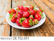 Купить «Fresh red strawberries in a white bowl standing on the rustic wooden table», фото № 28152691, снято 30 июля 2017 г. (c) FotograFF / Фотобанк Лори