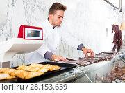 Купить «Seller in working clothes taking raw meat», фото № 28153639, снято 22 мая 2019 г. (c) Яков Филимонов / Фотобанк Лори