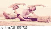 Купить «Smiling woman and guy training on beach by ocean», фото № 28153723, снято 8 декабря 2019 г. (c) Яков Филимонов / Фотобанк Лори