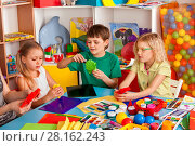Купить «School children with scissors in kids hands cutting paper.», фото № 28162243, снято 25 марта 2017 г. (c) Gennadiy Poznyakov / Фотобанк Лори