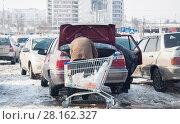 Купить «Мужчина загружает товар в багажник автомобиля», фото № 28162327, снято 5 марта 2018 г. (c) Владимир Казанков / Фотобанк Лори