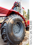 Купить «Big wheel of new modern agricultural tractor Kirovets K 4 exhibited at the annual Volga agro-industrial exhibition», фото № 28162643, снято 23 сентября 2017 г. (c) FotograFF / Фотобанк Лори