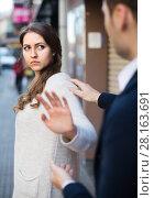 Купить «Boring male person accosting to female at crowded street», фото № 28163691, снято 17 октября 2018 г. (c) Яков Филимонов / Фотобанк Лори