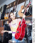 Купить «Brunette girl choosing acoustic guitar», фото № 28163763, снято 11 февраля 2016 г. (c) Татьяна Яцевич / Фотобанк Лори