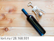 a bottle of red wine and a corkscrew on wooden boards top view close-up. Стоковое фото, фотограф Константин Лабунский / Фотобанк Лори