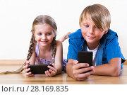 Купить «Smiling boy and girl playing with mobile phones», фото № 28169835, снято 25 сентября 2018 г. (c) Яков Филимонов / Фотобанк Лори