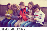 Купить «Children playing with mobile phones», фото № 28169839, снято 21 апреля 2019 г. (c) Яков Филимонов / Фотобанк Лори