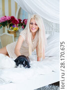 Купить «Pretty young blonde strokes fluffy black rabbit on white bed in room», фото № 28170675, снято 20 ноября 2015 г. (c) Losevsky Pavel / Фотобанк Лори