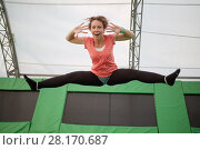 Купить «Young woman jumps on trampoline attraction making leg-split and grimacing by face», фото № 28170687, снято 29 августа 2016 г. (c) Losevsky Pavel / Фотобанк Лори
