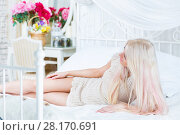 Купить «Pretty young blonde poses on white bed with pillows in cozy bedroom», фото № 28170691, снято 20 ноября 2015 г. (c) Losevsky Pavel / Фотобанк Лори