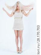 Купить «Blonde in short dress and heels shakes her hair at white studio», фото № 28170703, снято 20 ноября 2015 г. (c) Losevsky Pavel / Фотобанк Лори