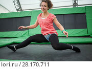 Купить «Young woman jumps on trampoline attraction in sitting position», фото № 28170711, снято 29 августа 2016 г. (c) Losevsky Pavel / Фотобанк Лори