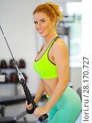 Купить «Beautiful woman does exercises on simulator in gym and smiles, shallow dof», фото № 28170727, снято 29 июня 2016 г. (c) Losevsky Pavel / Фотобанк Лори