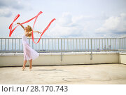 Купить «Woman with blond hair in white standing on tiptoe with red curly ribbon on the roof of a multistory building», фото № 28170743, снято 30 июля 2015 г. (c) Losevsky Pavel / Фотобанк Лори