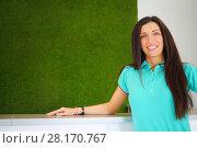 Купить «Young woman in t-shirt stands near desk of reception with green wall», фото № 28170767, снято 29 июня 2016 г. (c) Losevsky Pavel / Фотобанк Лори
