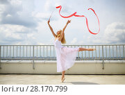 Купить «Pretty gymnast in white with raised hands with red curly ribbon standing on a leg on the roof of a multistory building», фото № 28170799, снято 30 июля 2015 г. (c) Losevsky Pavel / Фотобанк Лори
