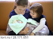 Купить «Two happy sisters hold together newborn in blanket on sofa in room», фото № 28171051, снято 22 марта 2016 г. (c) Losevsky Pavel / Фотобанк Лори