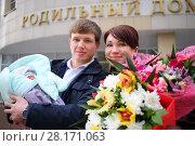 Купить «Man with newborn, woman with flowers stand near maternity hospital, text - maternity hospital», фото № 28171063, снято 22 марта 2016 г. (c) Losevsky Pavel / Фотобанк Лори