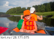 Happy little boy and woman in life-jackets sail on inflatable boat on river at summer, focus on child. Стоковое фото, фотограф Losevsky Pavel / Фотобанк Лори