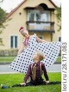Купить «Boy sitting on side split and girl in polka-dotted dress standing behind him on grassy lawn look at each other against two-storied house», фото № 28171083, снято 10 сентября 2016 г. (c) Losevsky Pavel / Фотобанк Лори