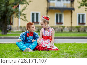Smiling boy and girl in dancing suits sit on grassy lawn and look at each other against two-storied house. Стоковое фото, фотограф Losevsky Pavel / Фотобанк Лори