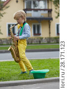 Купить «Little boy in dancing suit plays saxophone on grassy lawn against two-storied house near road, hat for earnings lies on grass», фото № 28171123, снято 10 сентября 2016 г. (c) Losevsky Pavel / Фотобанк Лори