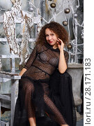 Купить «Curly smiling woman in transparent dress sits in white stylish studio», фото № 28171183, снято 27 ноября 2015 г. (c) Losevsky Pavel / Фотобанк Лори