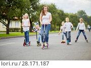 Купить «Woman and five children on scooters, roller skates and skateboard ride on street », фото № 28171187, снято 10 сентября 2016 г. (c) Losevsky Pavel / Фотобанк Лори