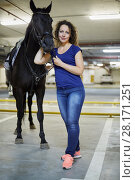 Купить «Young woman with horse at underground parking», фото № 28171251, снято 5 июля 2016 г. (c) Losevsky Pavel / Фотобанк Лори